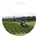 Round image of a small helicopter flying over vineyards