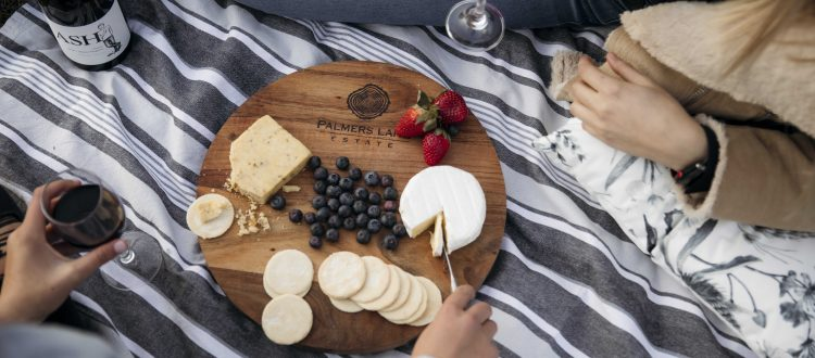 top angle shot of a cheeseboard with two girls sitting next to it drinking wine