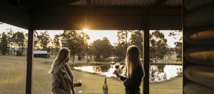two girls drinking a glass of wine on a balcony looking into the distance